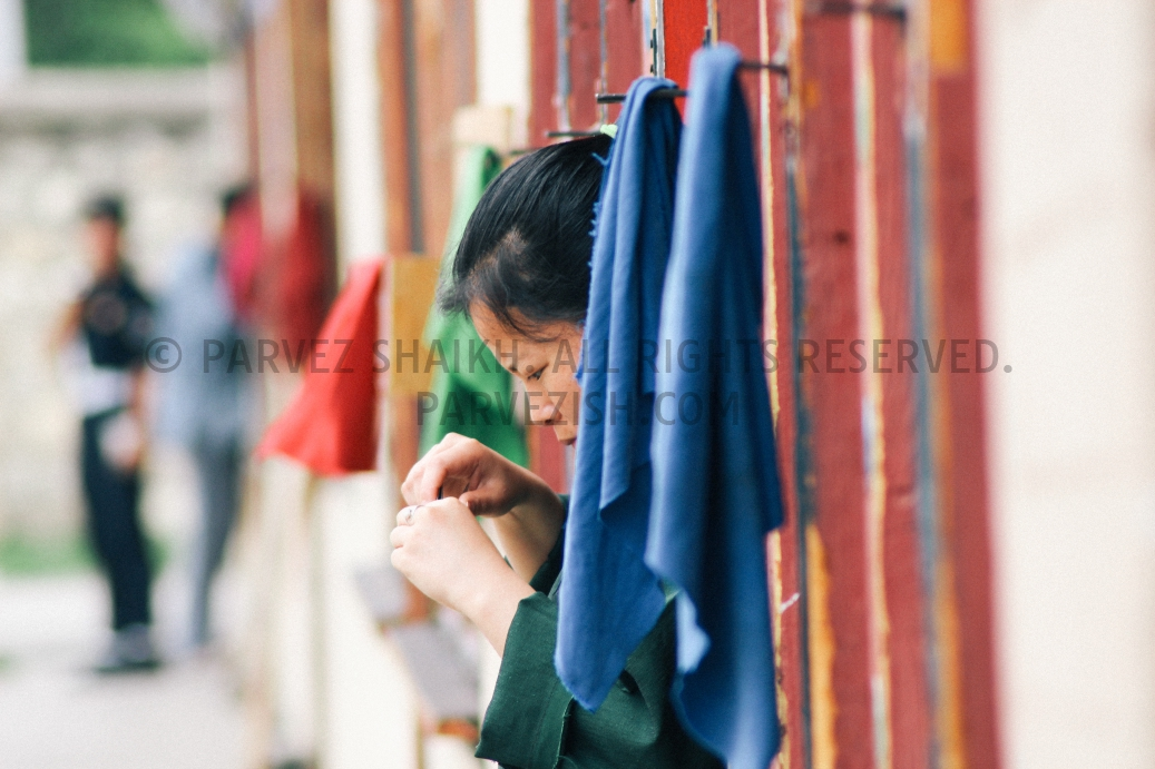 Photo of a young Bhutanese girl clipping her nail