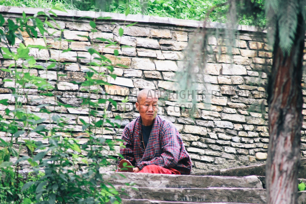 A Buddhist monk sitting outside a temple in Thimphu, Bhutan