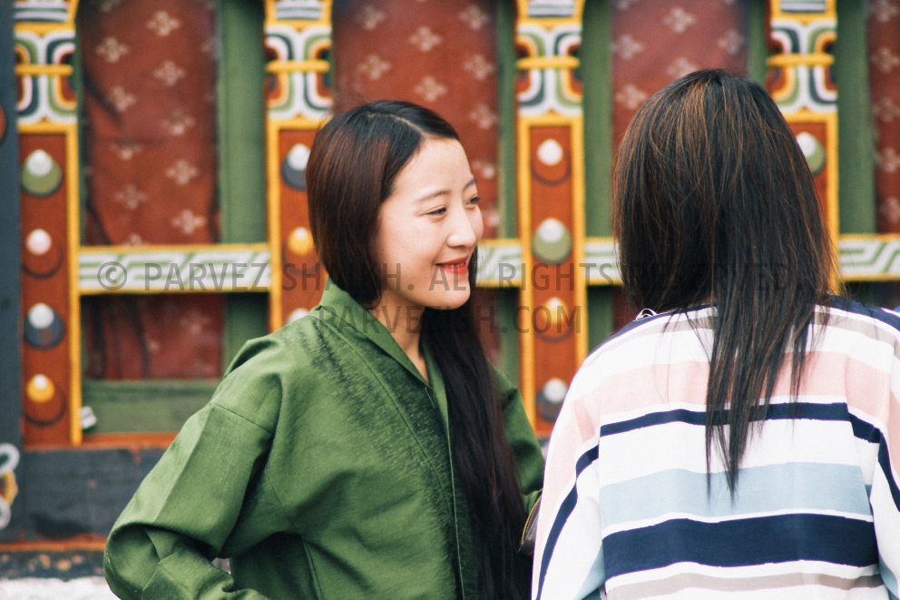 A young girl is talking to tourists at a monastery in Thimphu