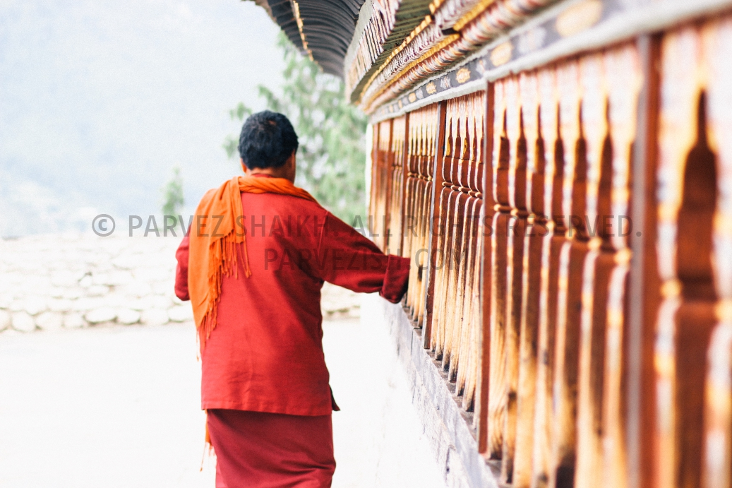 A Bhutanese lady is photographed spinning prayer wheels