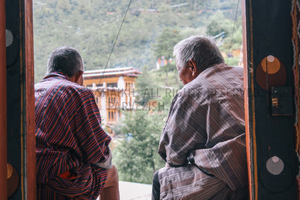 Two elderly Bhutanese men are busy in a conversation at Changangkha Lhakhang