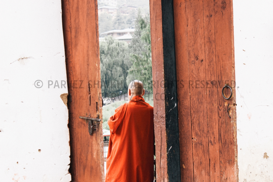 A Buddhist monk is standing by a door of Changangkha Lhakhang, Thimphu