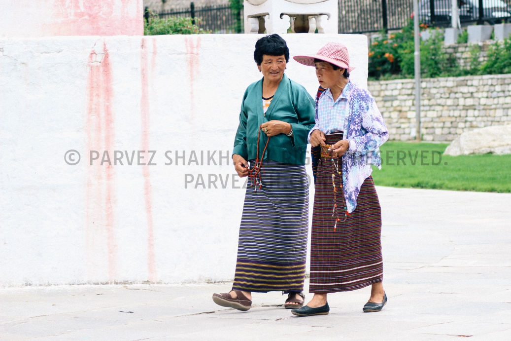 Two ladies circling around Memorial Chorten while having a conversation