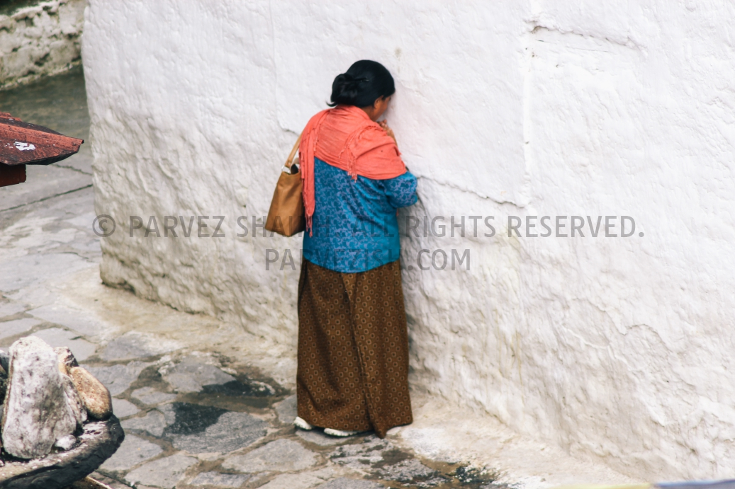 A Bhutanese lady is photographed praying by resting her head against a wall.