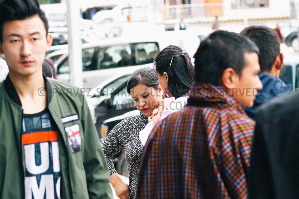 Two women are having a conversation in a busy Thimphu street