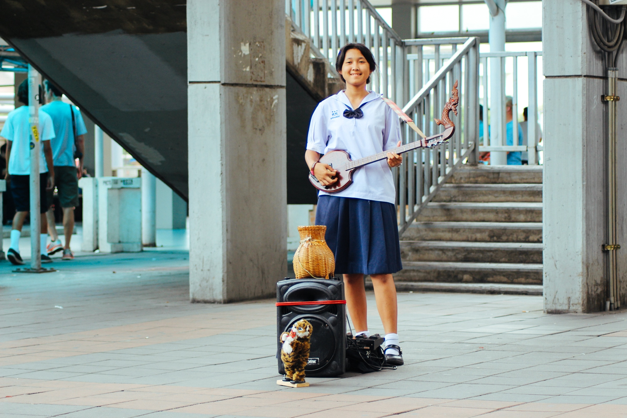 A girl performs near a metro station in Bangkok to raise funds for her education