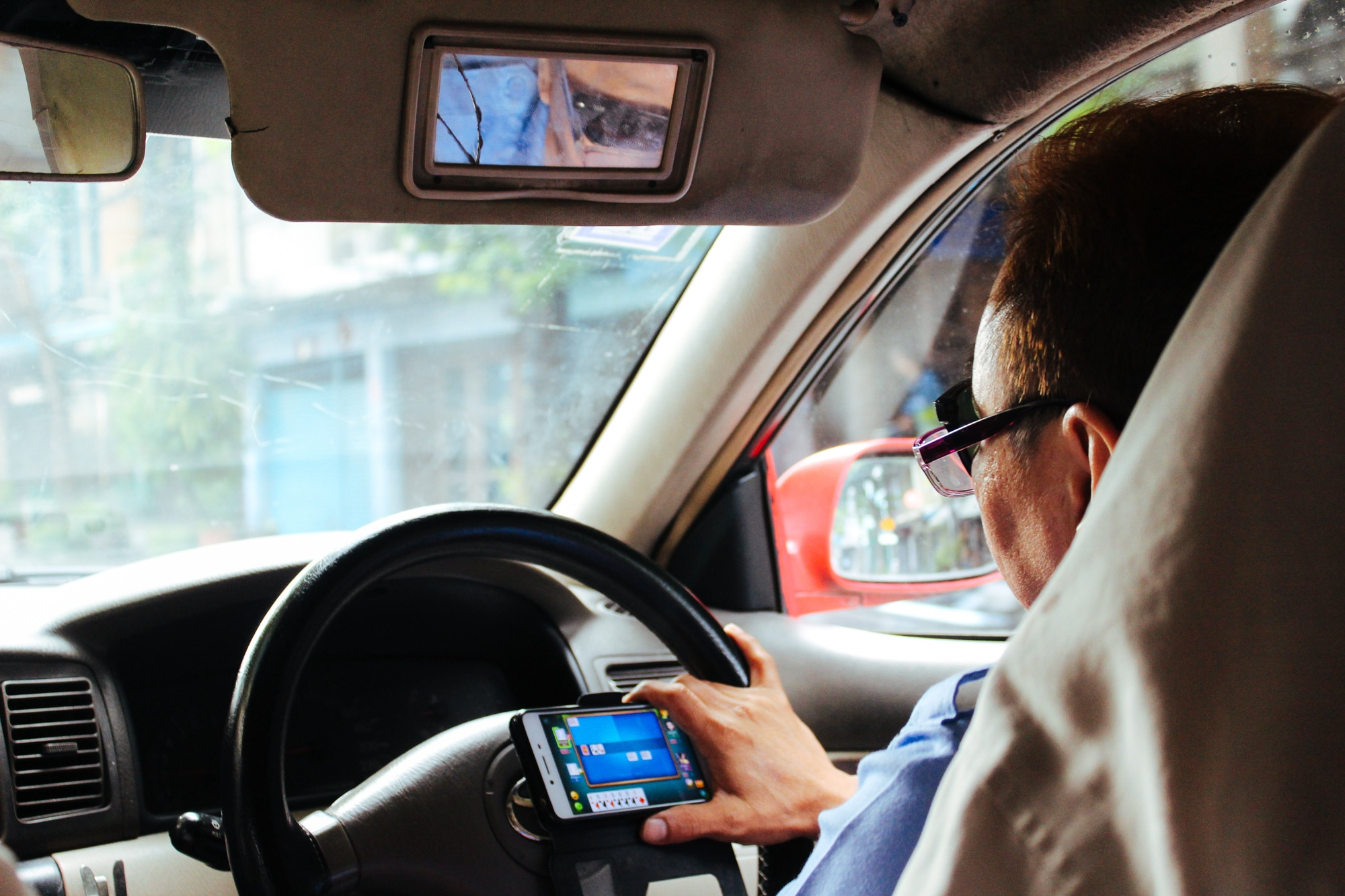 A taxi driver plays game on his phone as he drives through Bangkok