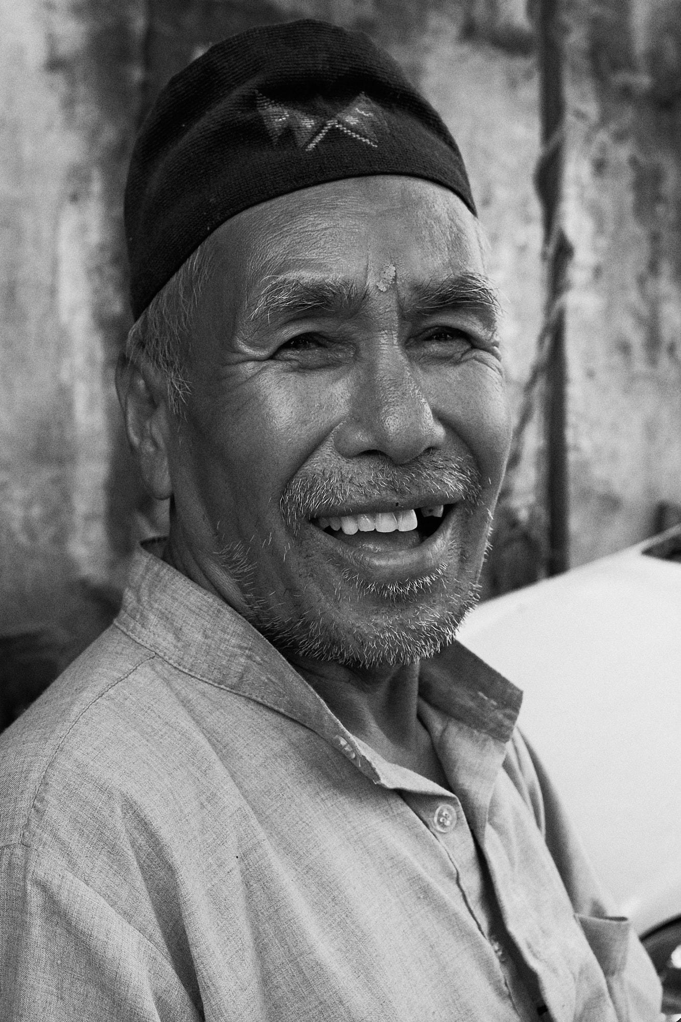An elderly Nepali man wearing Dhaka topi smiles at camera