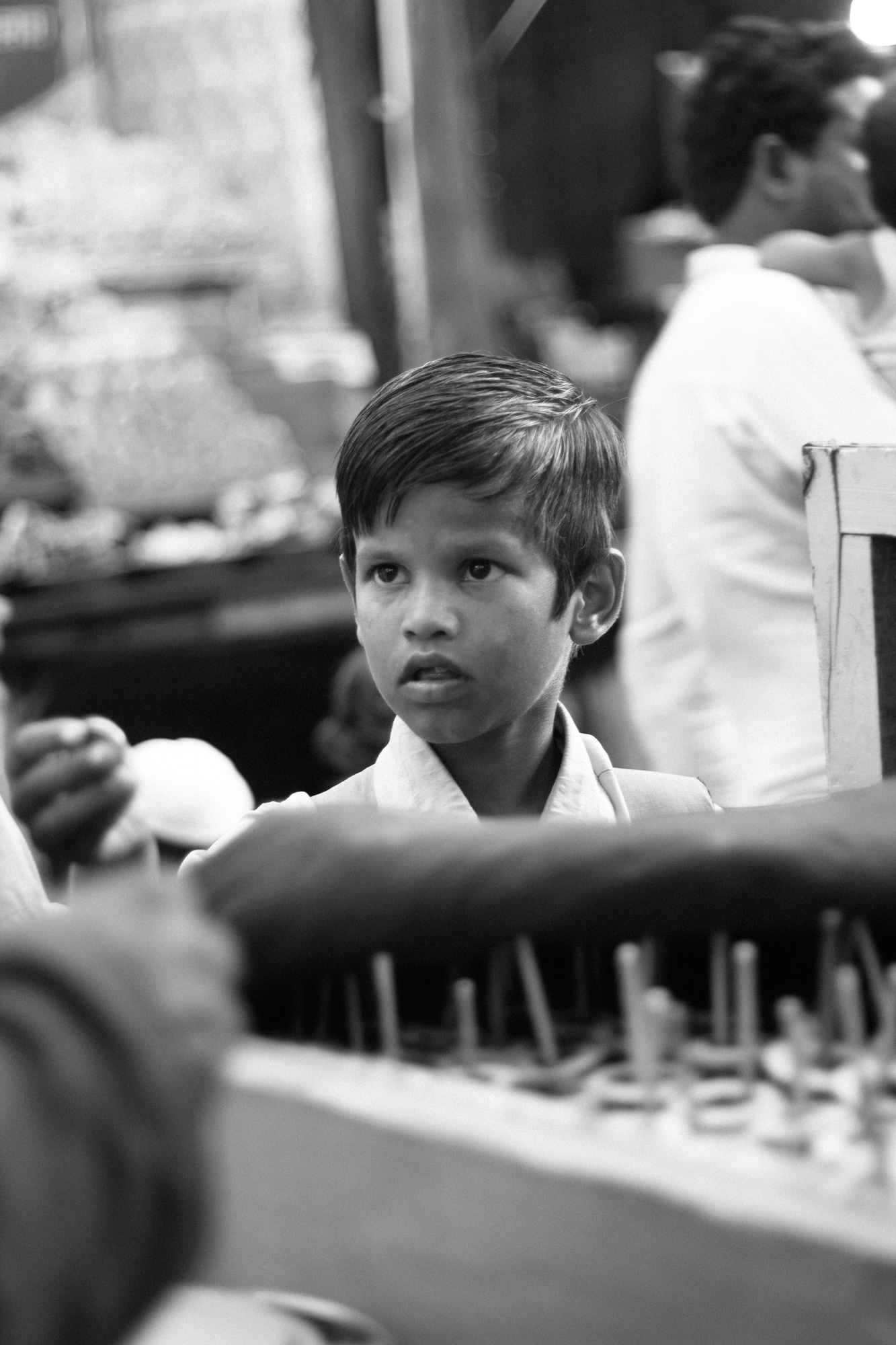 A boy returning from school stops to buy a kulfi.