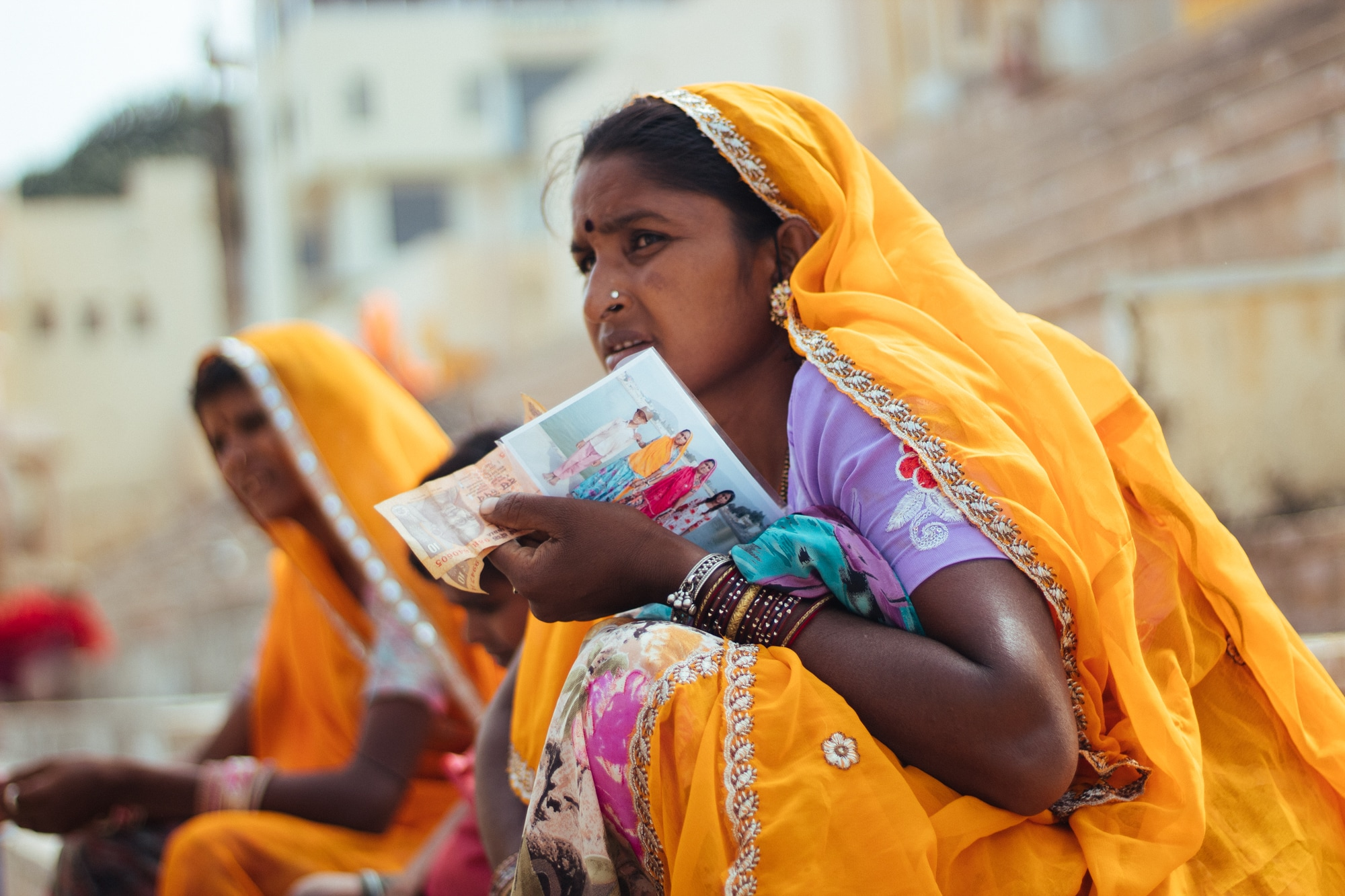 A woman holding picture of her family. Photographers carry portable printers at Pushkar ghat and offer instant photography service to visitors.