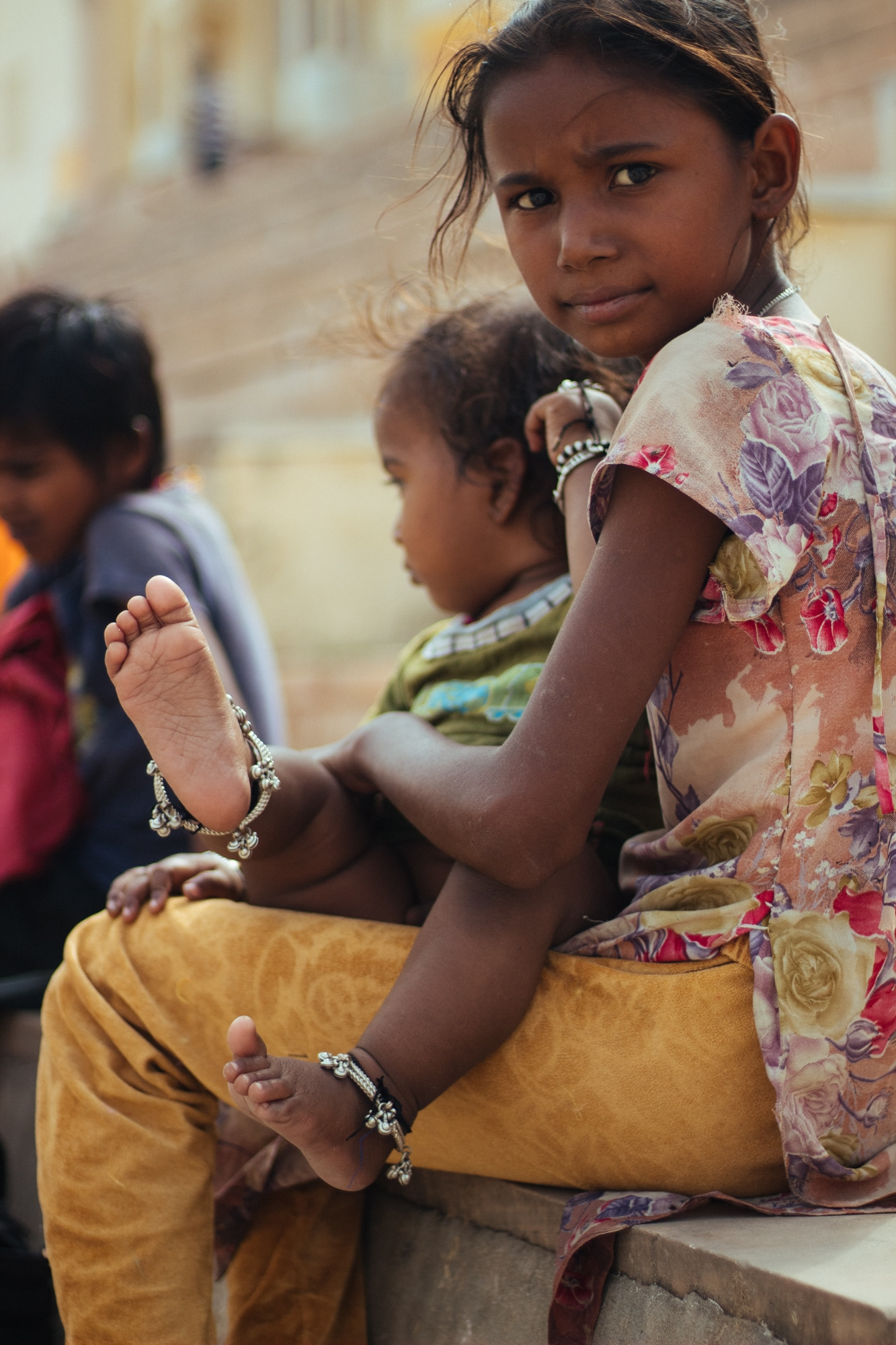 A young girl at Pushkar ghat holding a child.