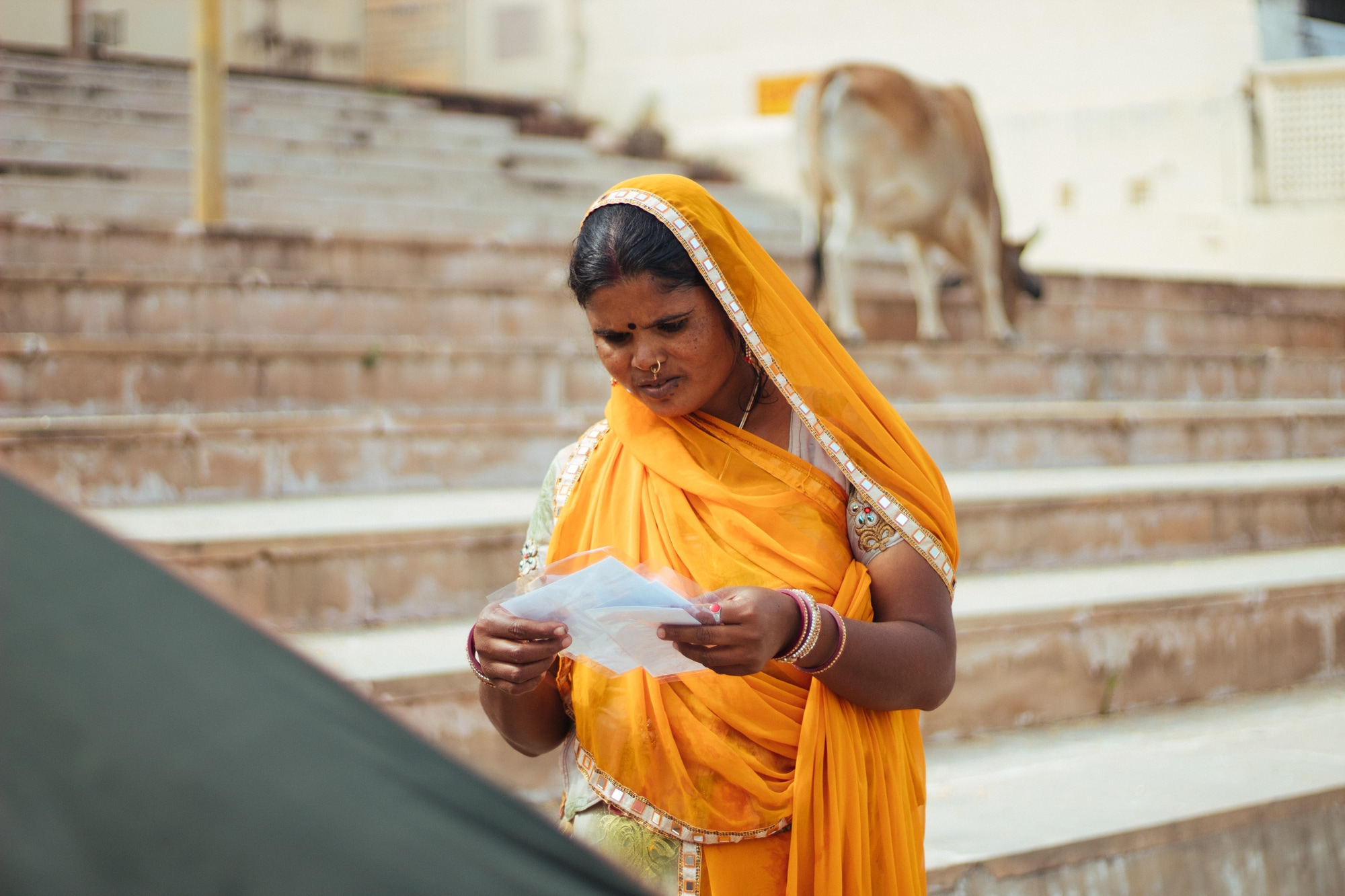 A woman looks at a picture she has just received. Photographers carry portable printers at Pushkar ghat and offer instant photography service to visitors.