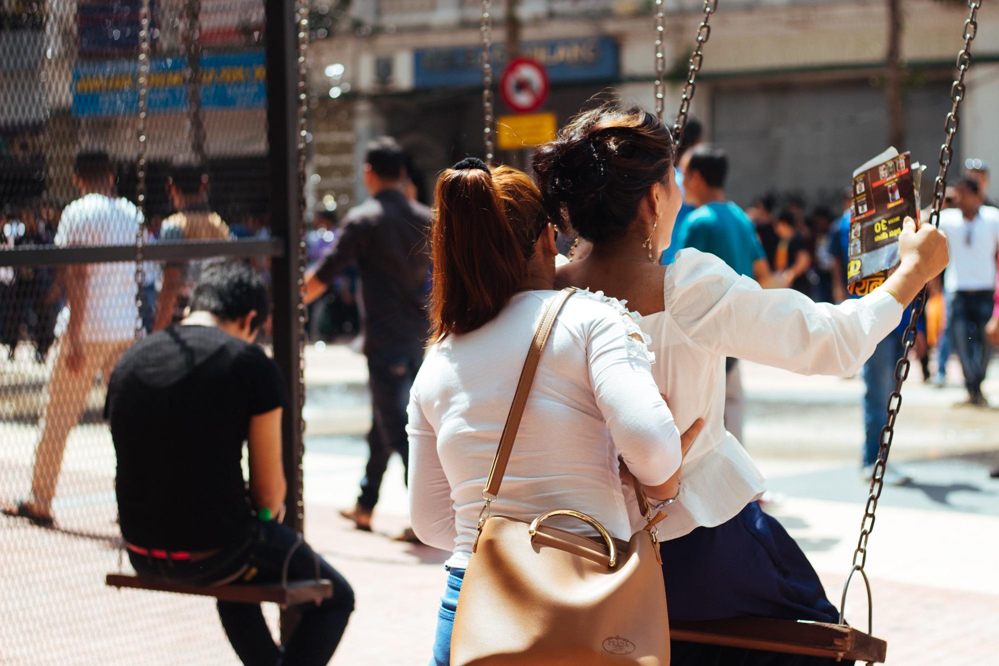 A woman helping her friend enjoy swing