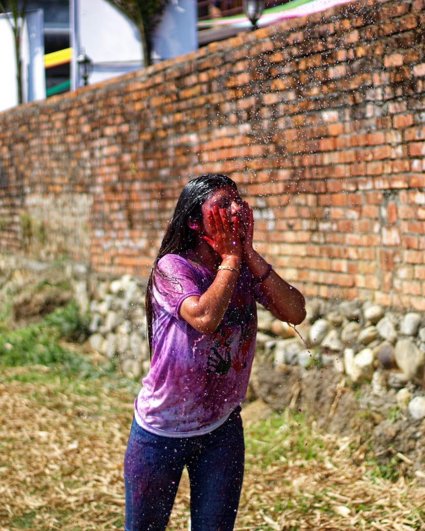 A Girl in Pokhara Washing Colours Off Her Face During Holi