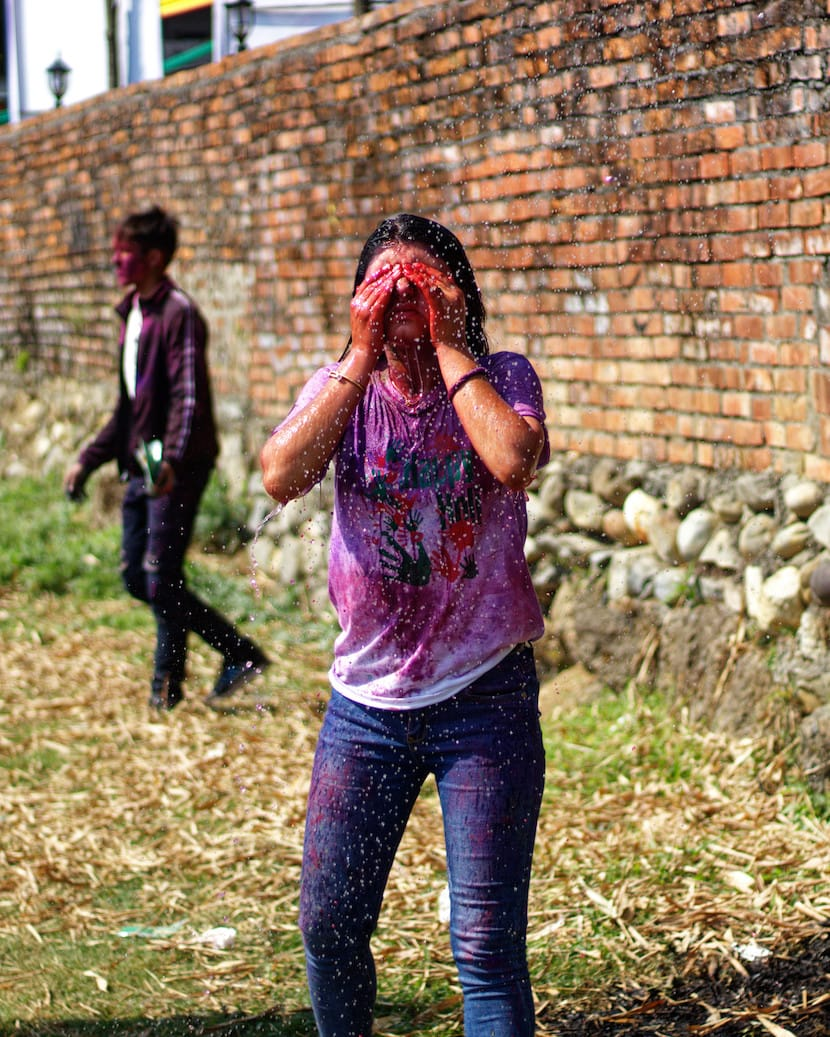 A Girl in Pokhara Washing Colours Off Her Face During Holi Celebration