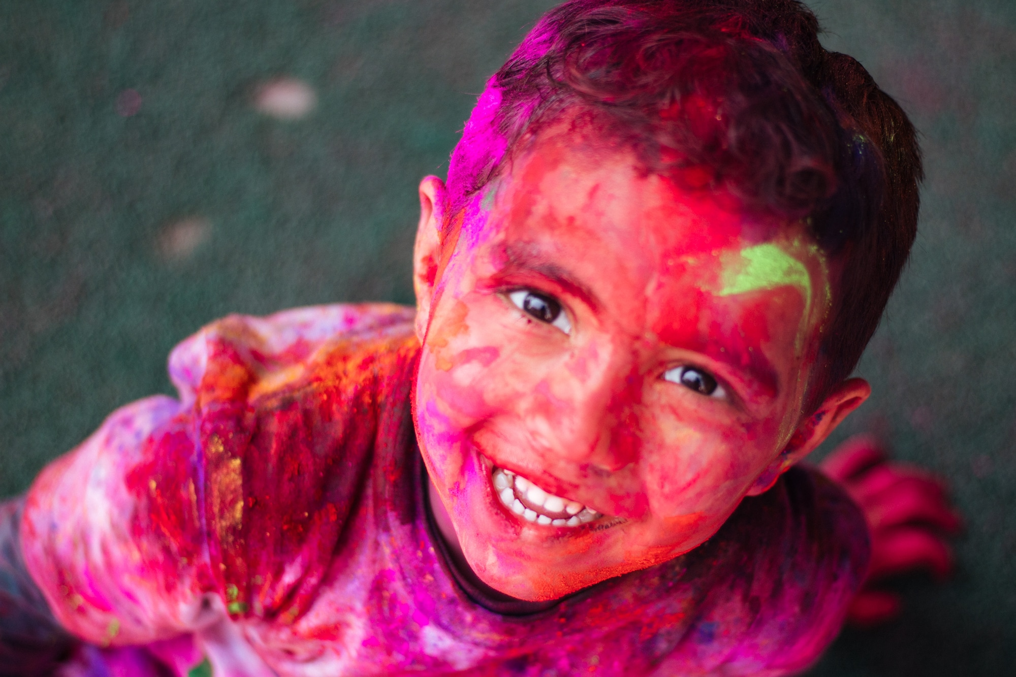 A young boy is completely covered in holi colours