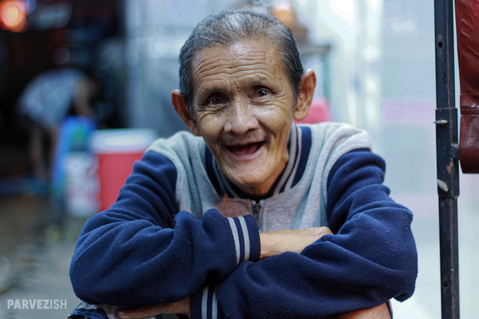 An Aged Man Smiling at Camera in A Street of Bangkok