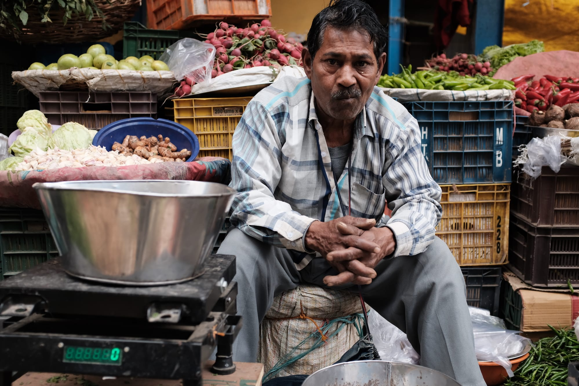 A Vegetable Vendor Looks at Camera