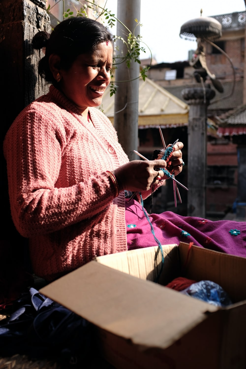 A woman knitting inside a temple complex in Bhaktapur