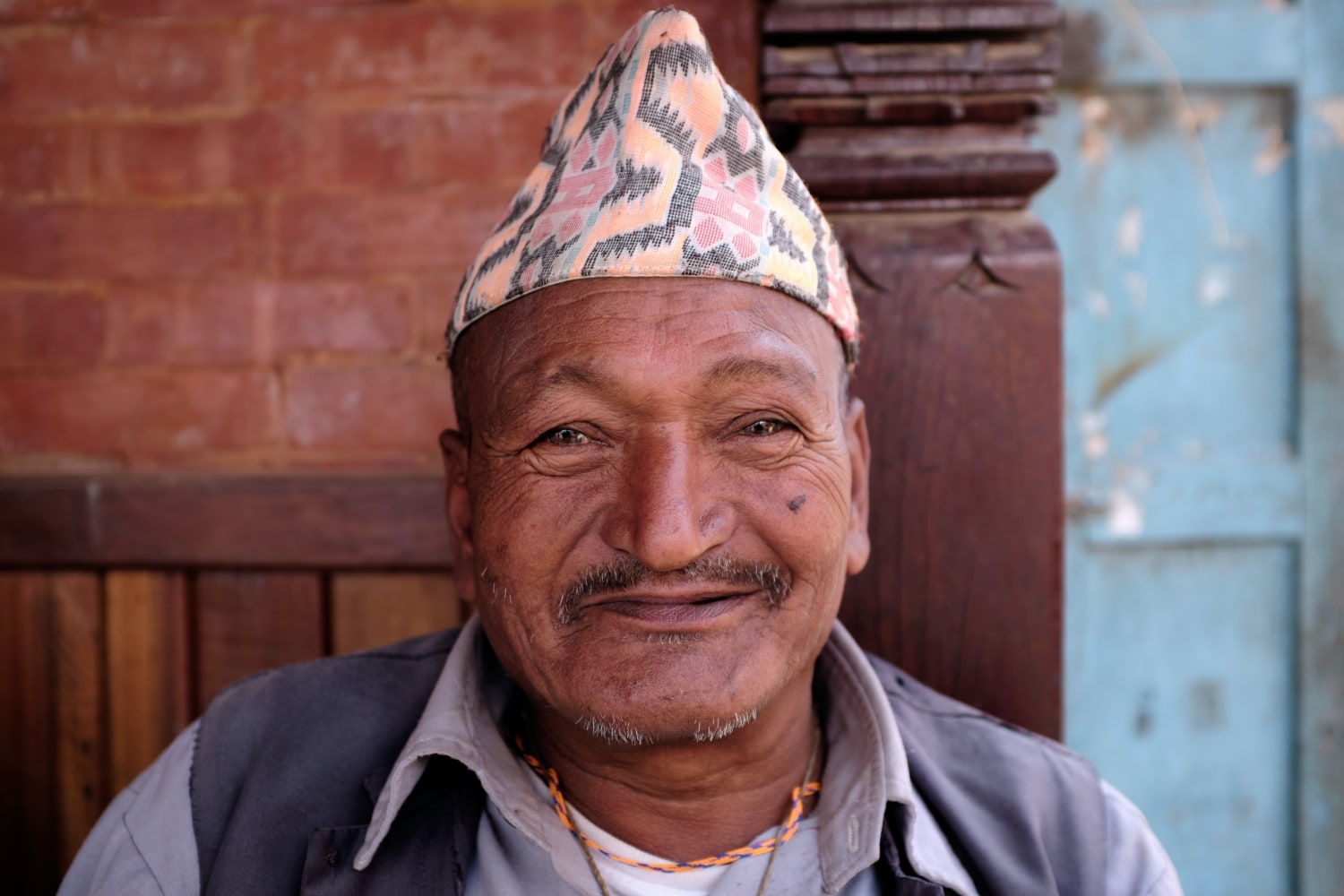 A Newari man wearing Dhaka topi smiles at camera