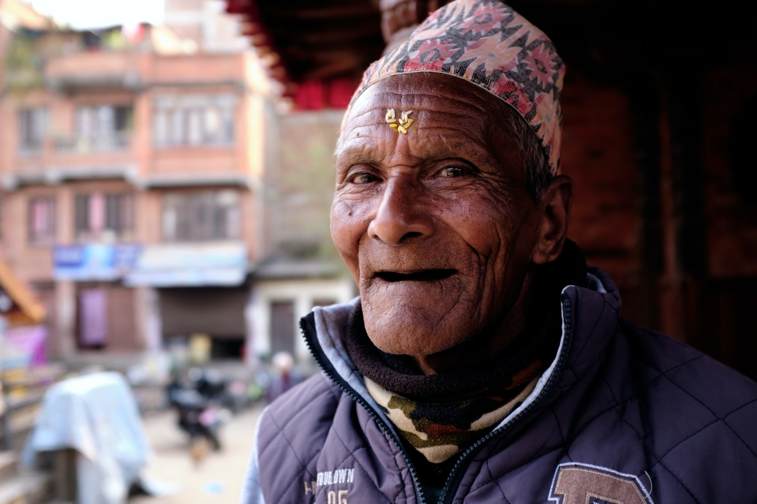 An old man wearing Dhaka topi smiles at camera
