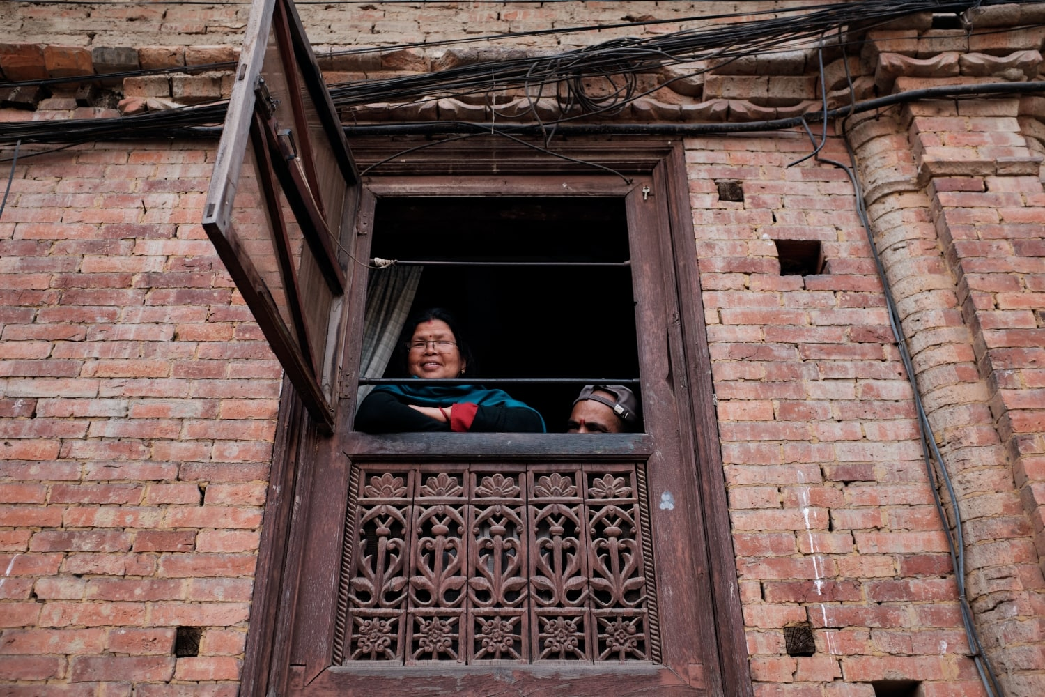 A couple sitting by a window of their house in Bhaktapur