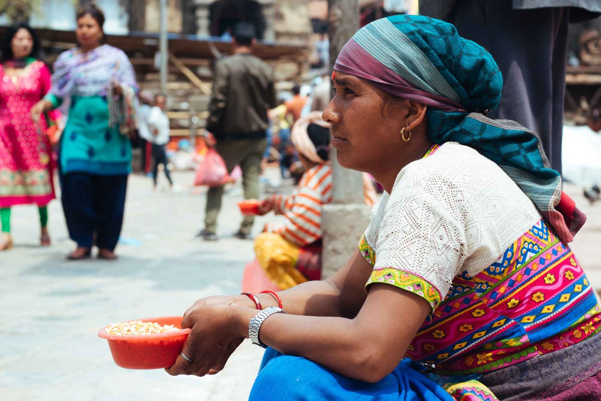 A woman selling corn to feed pigeons