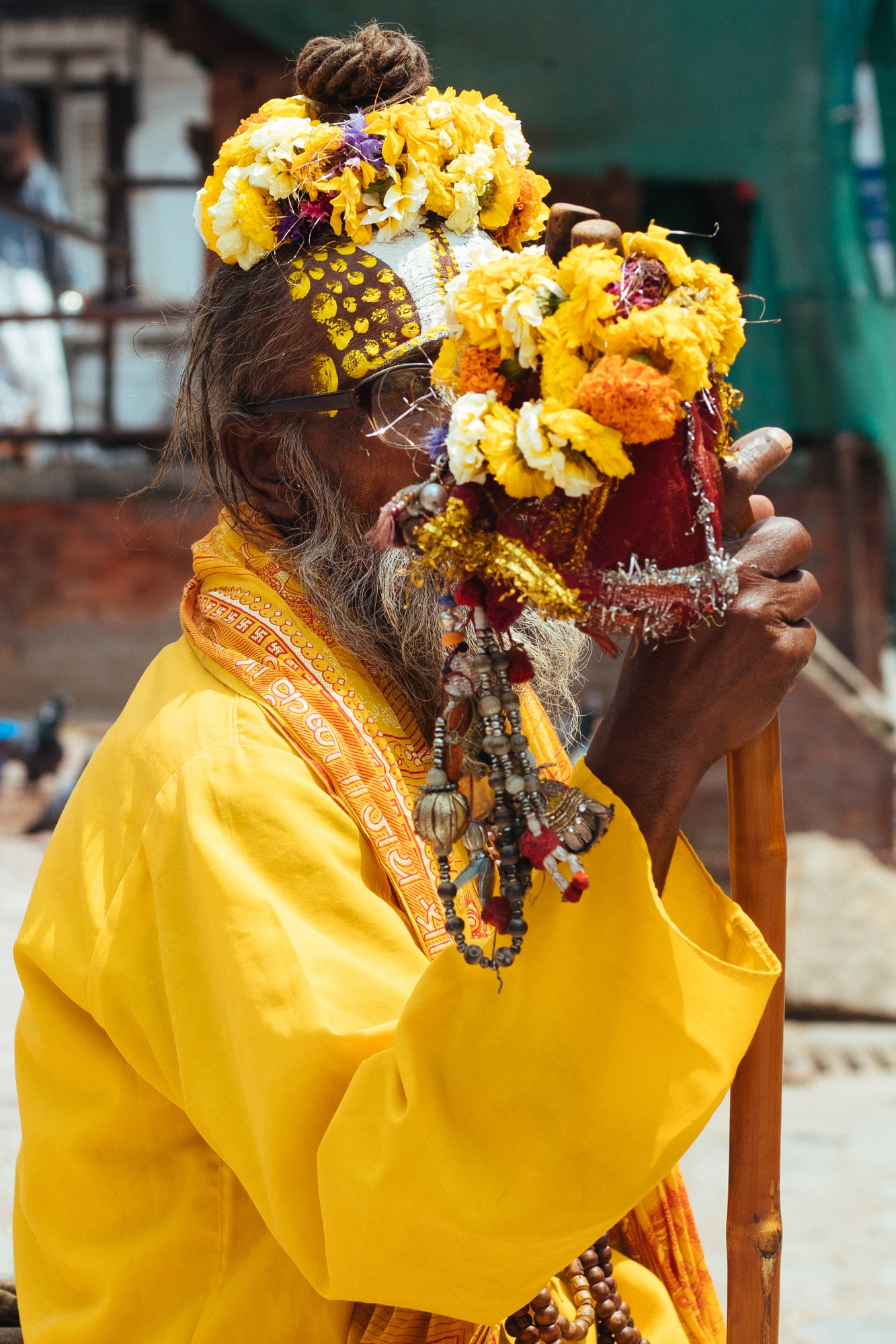 A sadhu in yellow looks at the camera