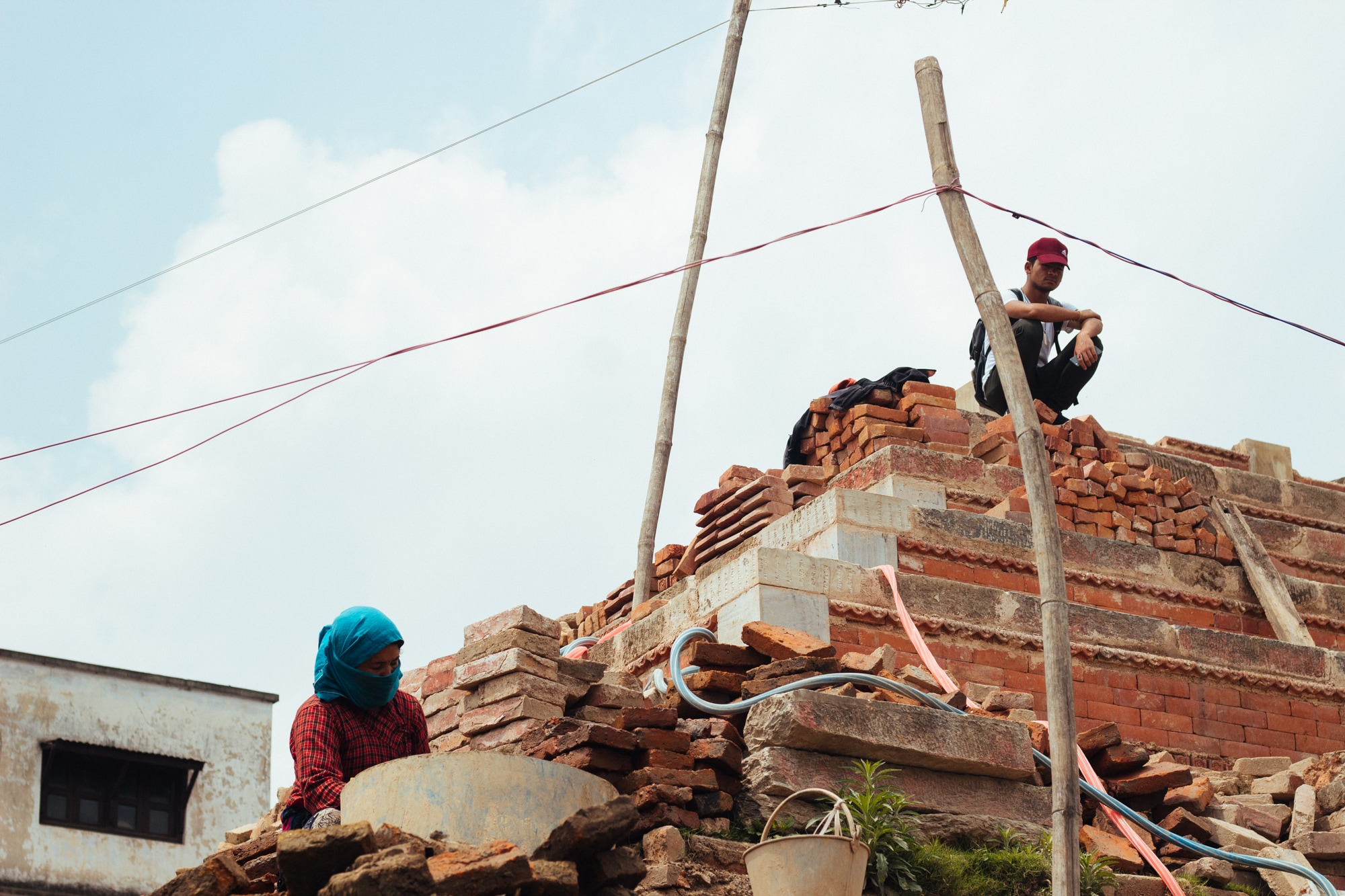 A man sitting on the debris of a temple damaged in 2015 earthquake as a woman works nearby