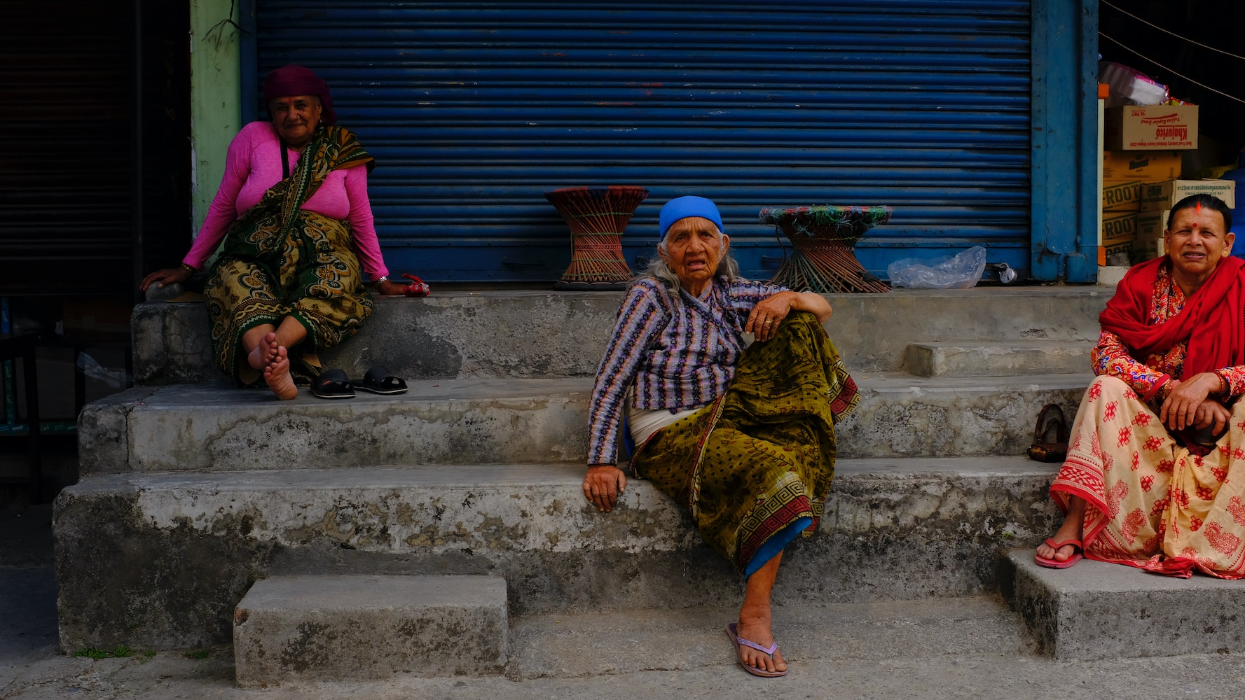 Aged women sitting outside a closed shop in Pokhara