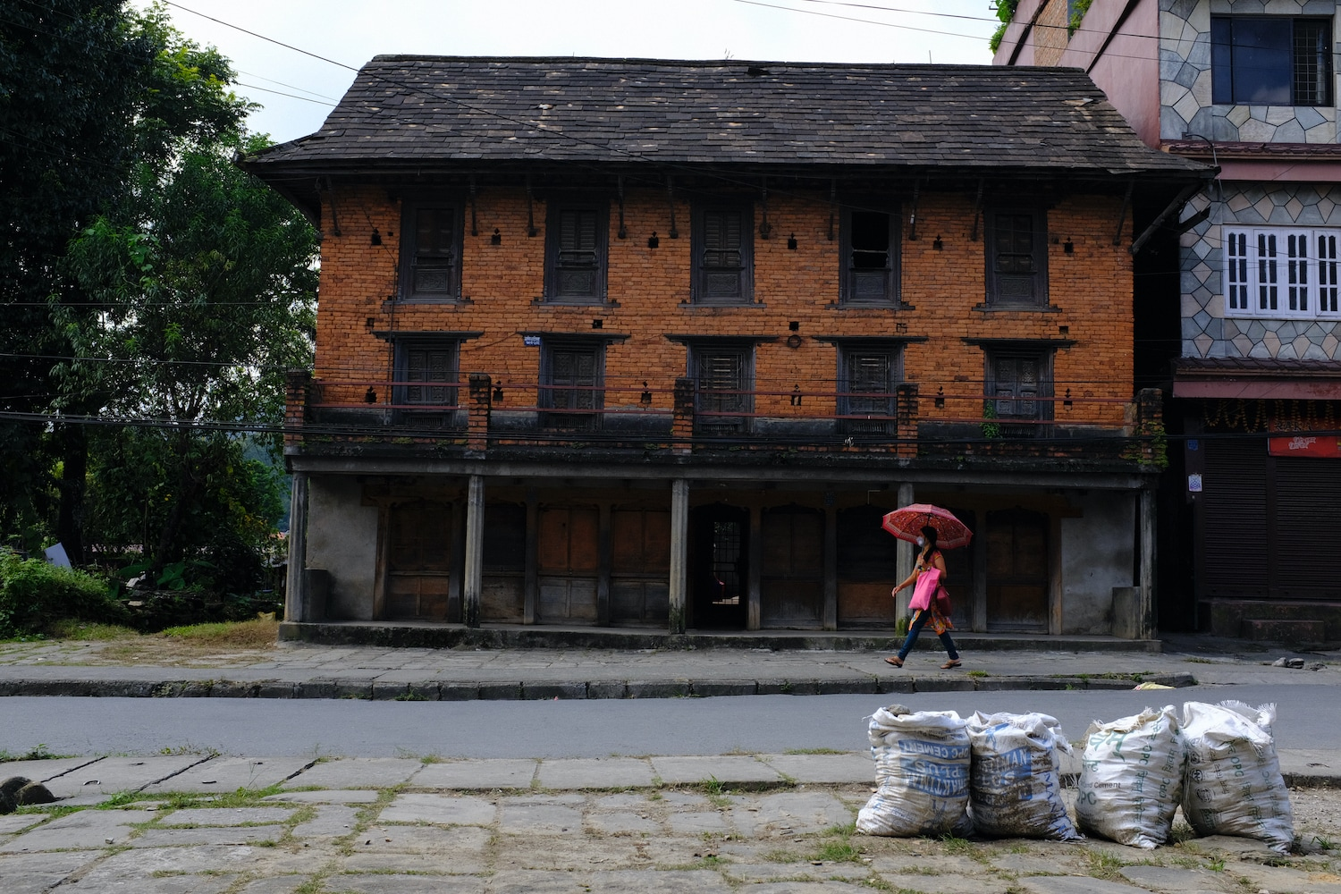 A woman passes by an old traditional house in Pokhara