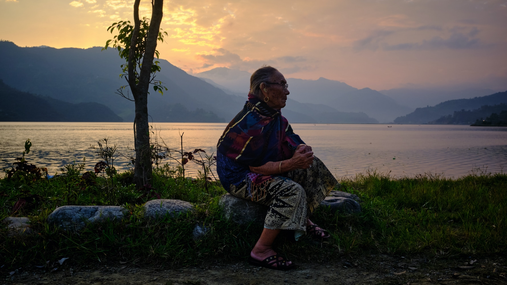 An elderly woman sitting by the Pokhara lakeside during sunset