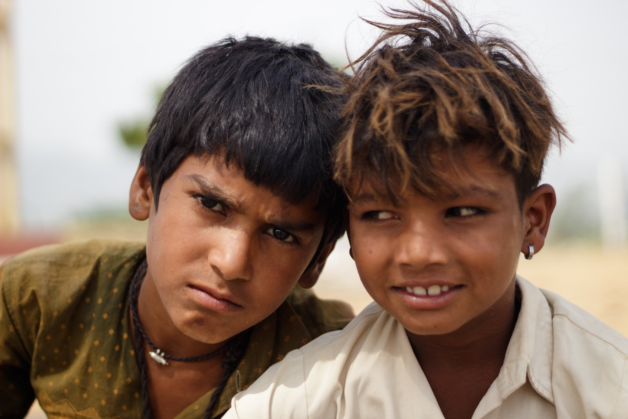 A young boy interrupts as his friend poses for a picture. Pushkar, Rajasthan.