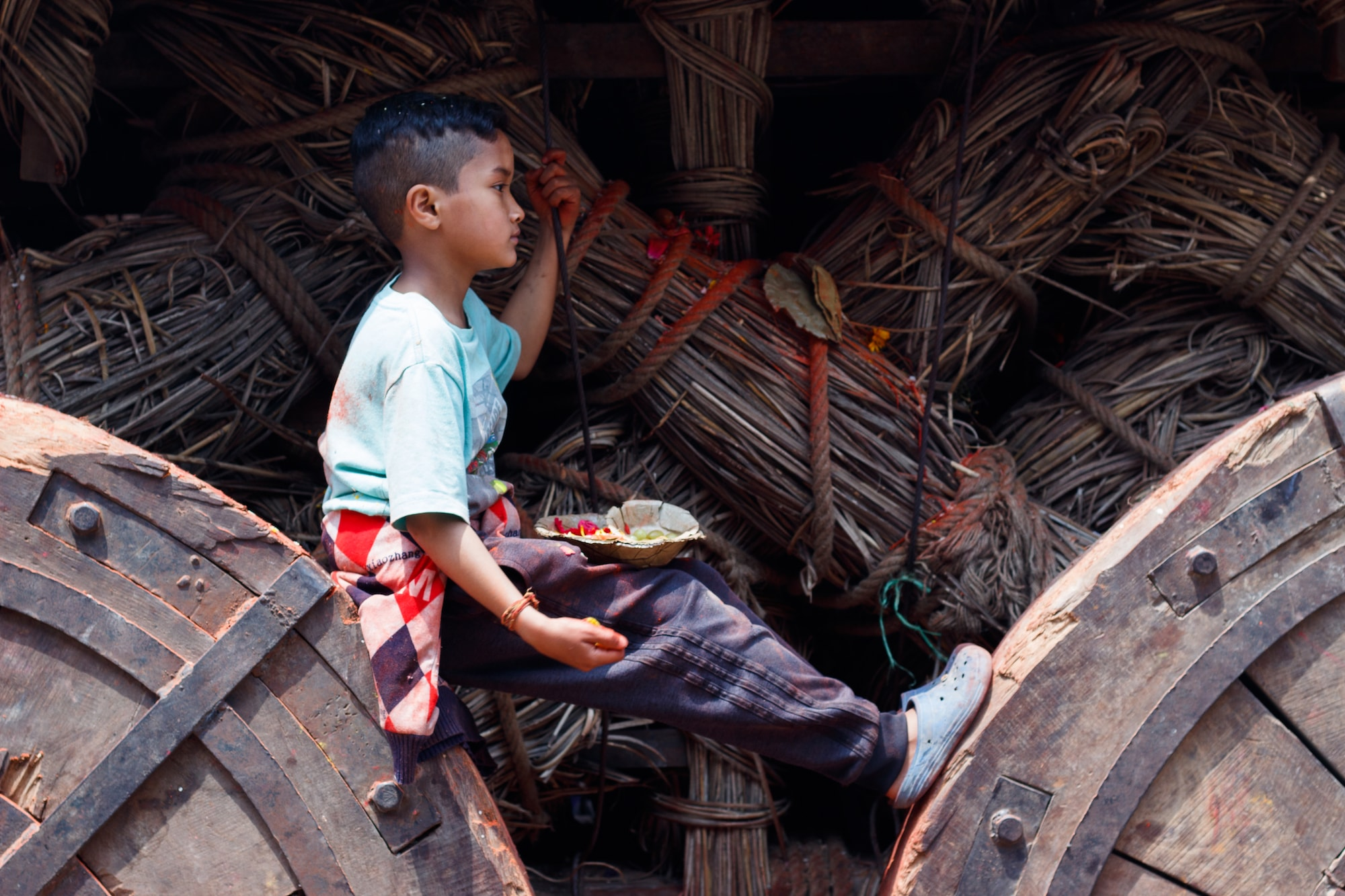 A young boy sitting between wheels of a giant chariot at Kathmandu Durbar Square