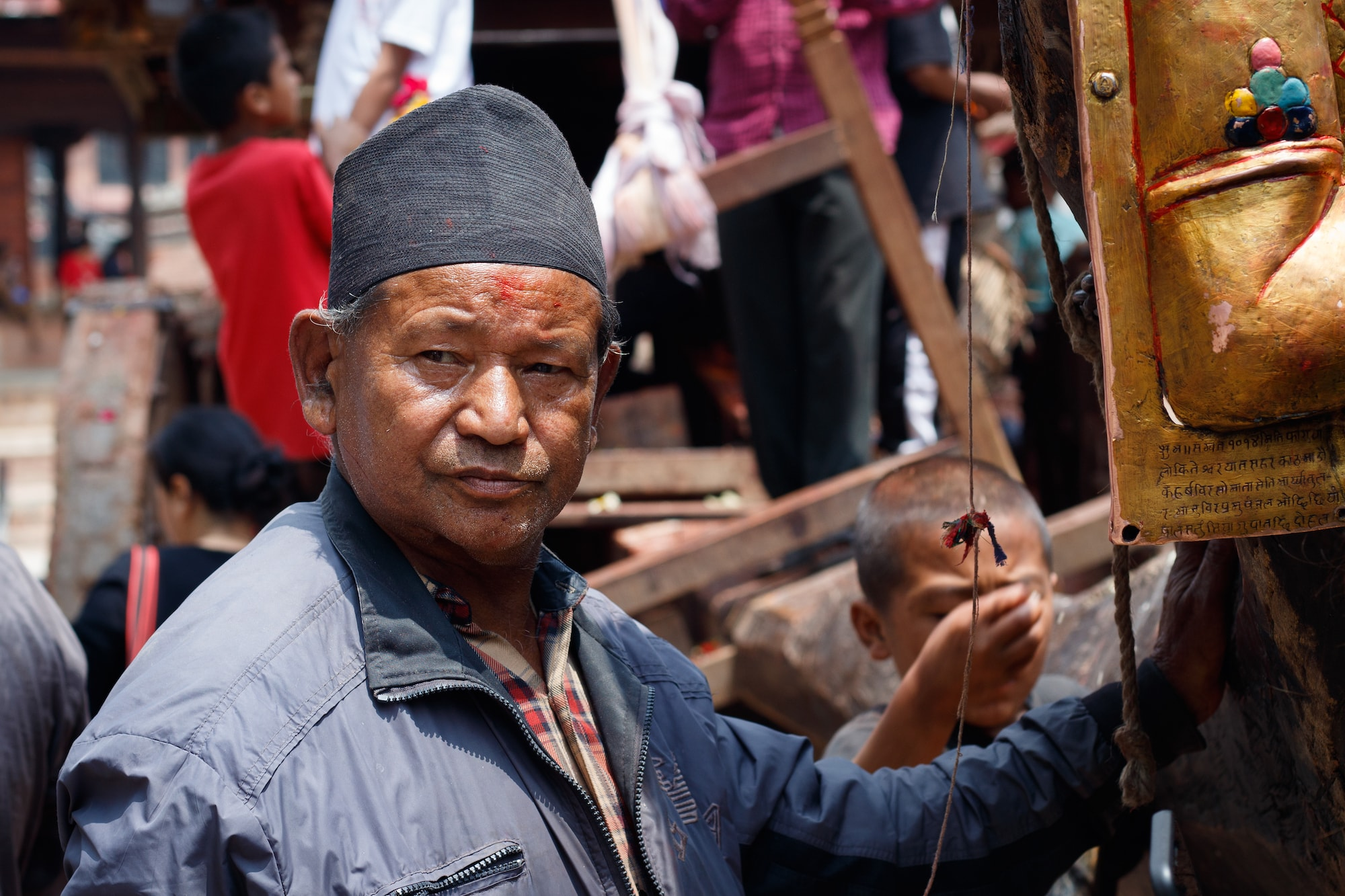 A man standing near a chariot during a religion ceremony at Kathmandu Durbar Square