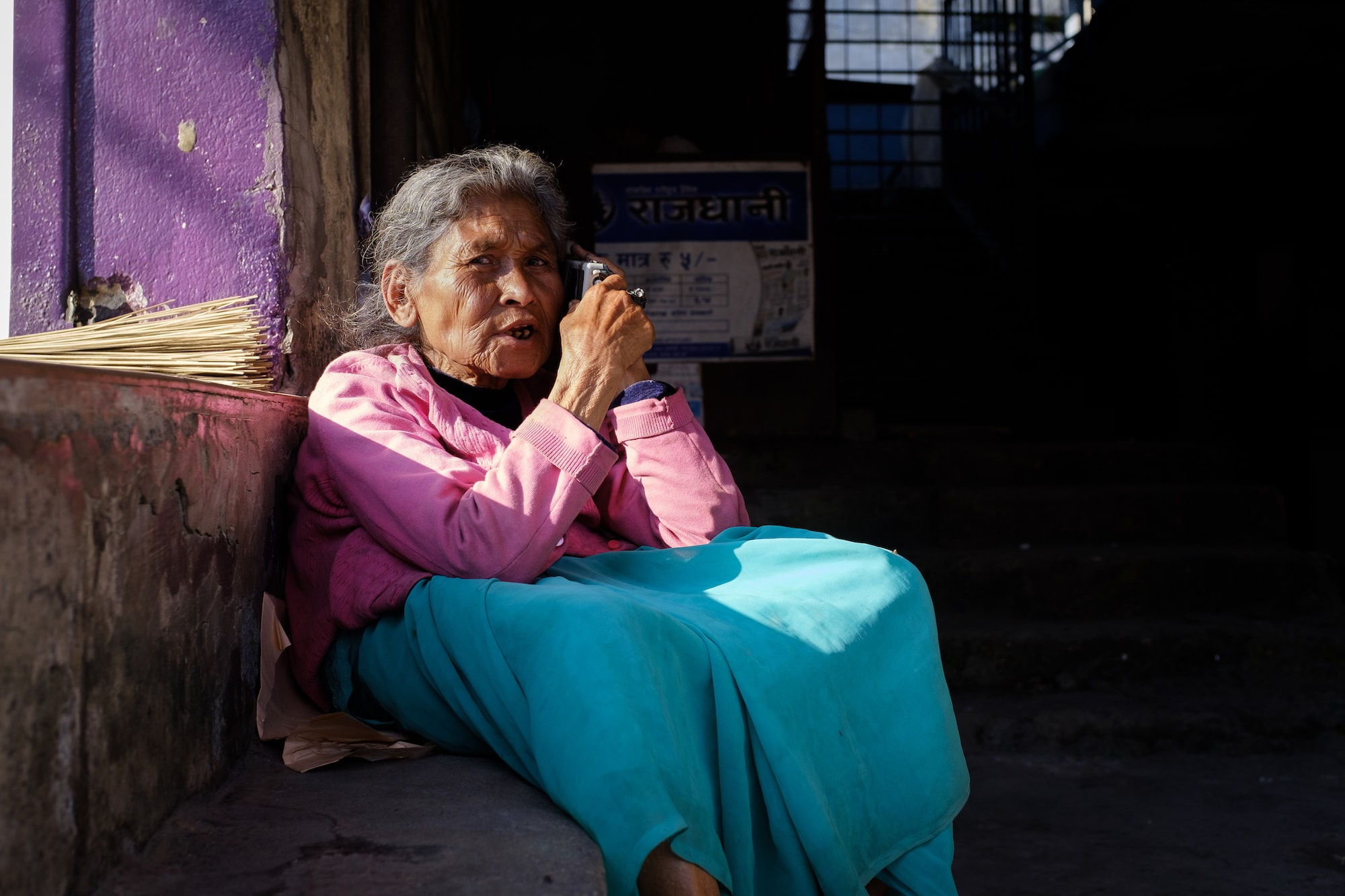 An elderly woman photographed listening to a radio in Pokhara