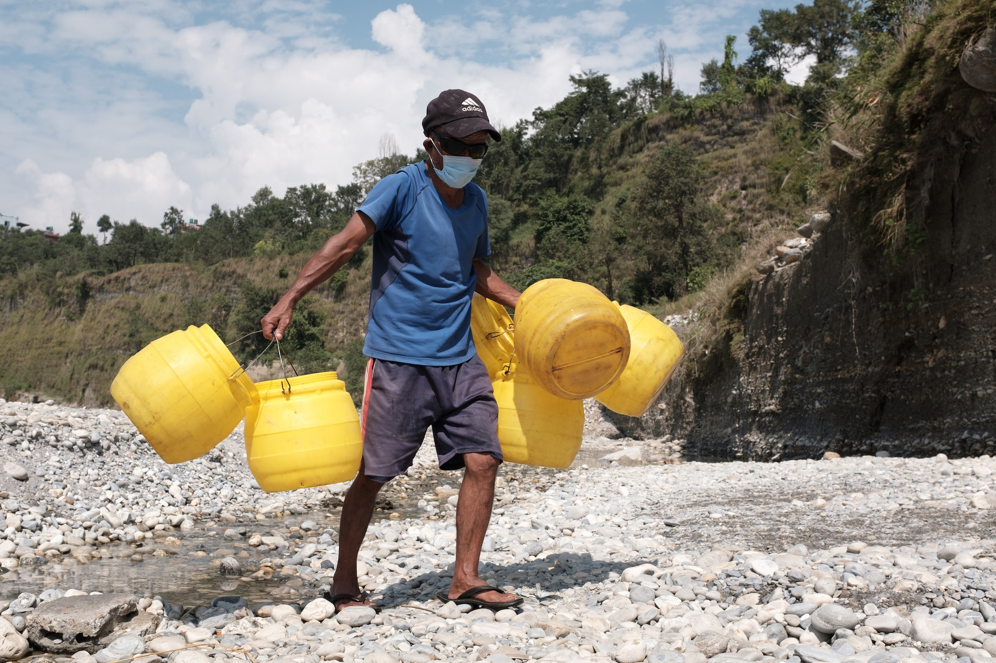 A man walking away with water buckets after washing them by riverside. Pokhara, Nepal