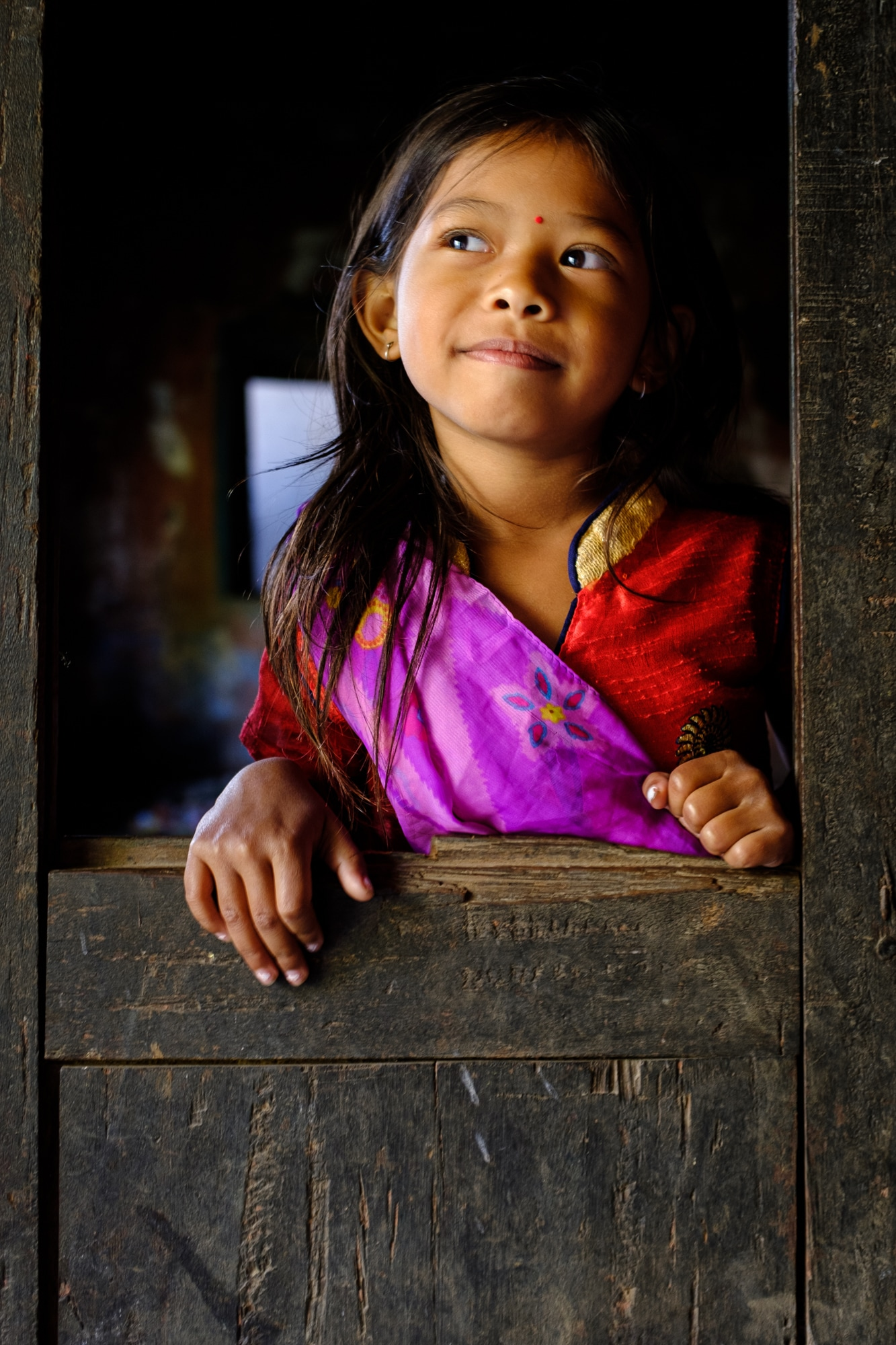 A young girl poses for a picture in Pokhara, Nepal