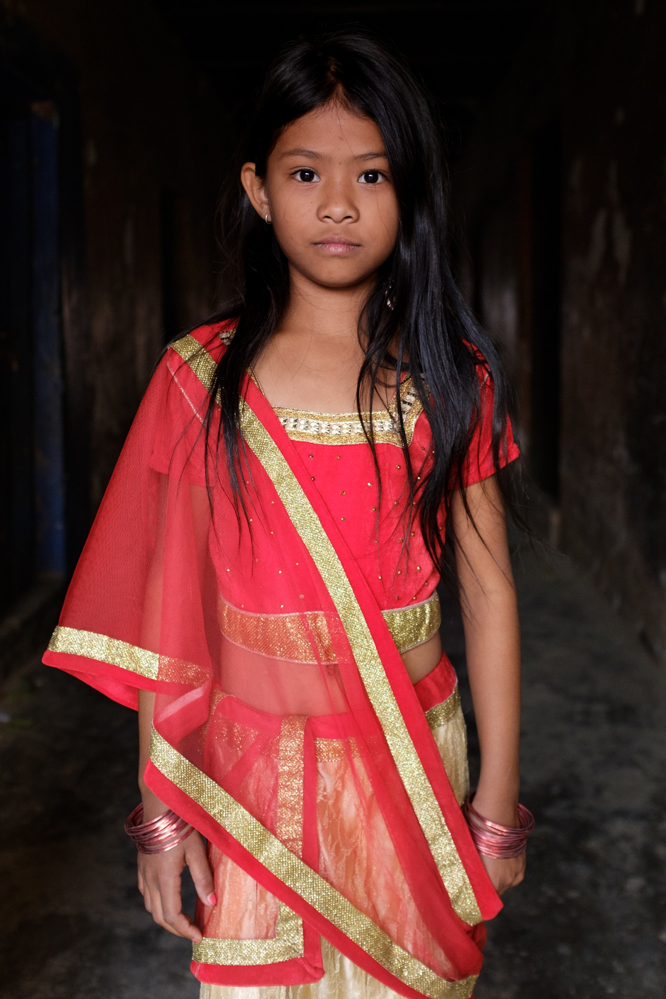 A young Nepali girl wearing festive clothes poses for a picture