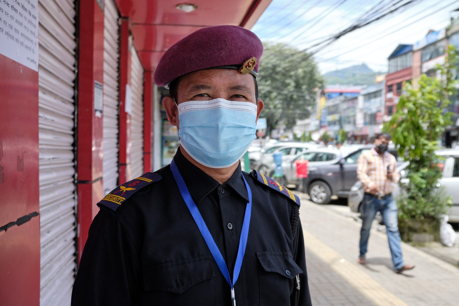 A security guard poses for a picture outside a closed shop in Pokhara.