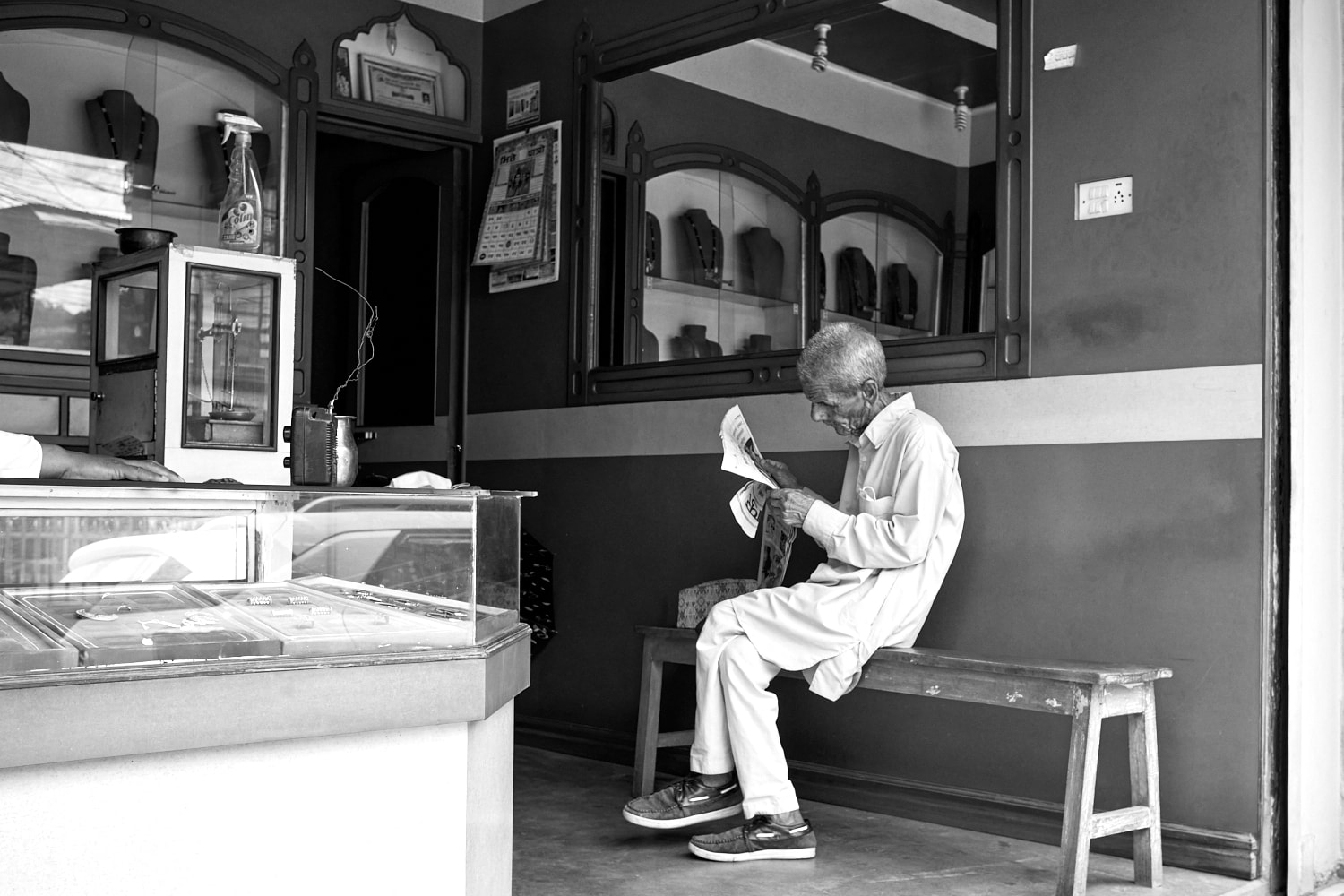 July 2021, Pokhara, Nepal: An elderly man reads a newspaper inside a shop as news plays on a radio with makeshift antenna