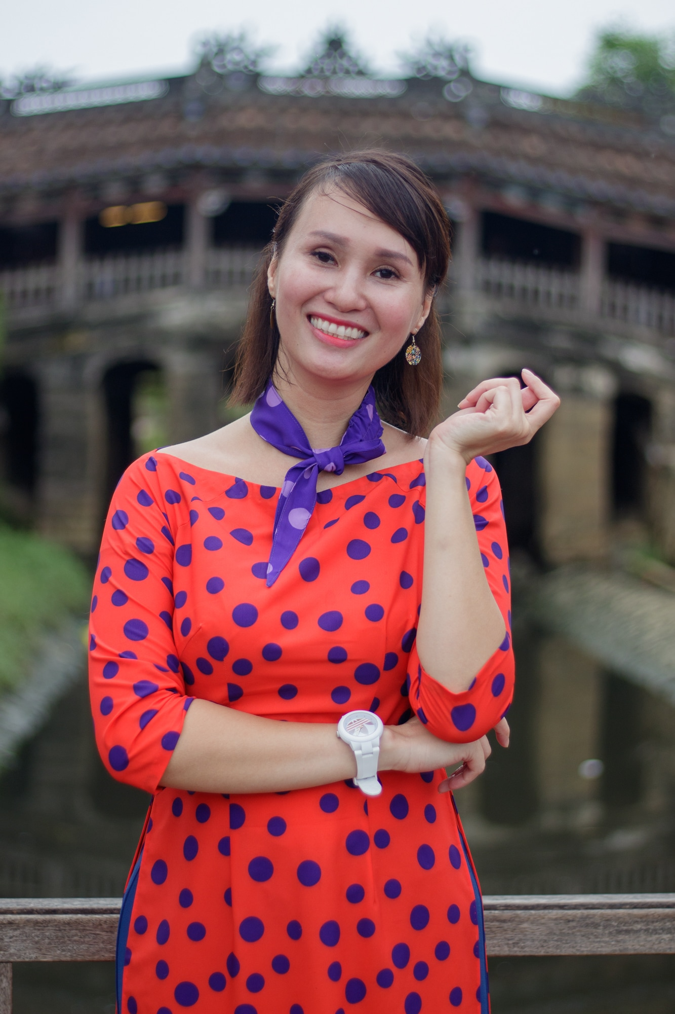 A woman poses for a picture in front of the Japanese Bridge in Hoi An, Vietnam.