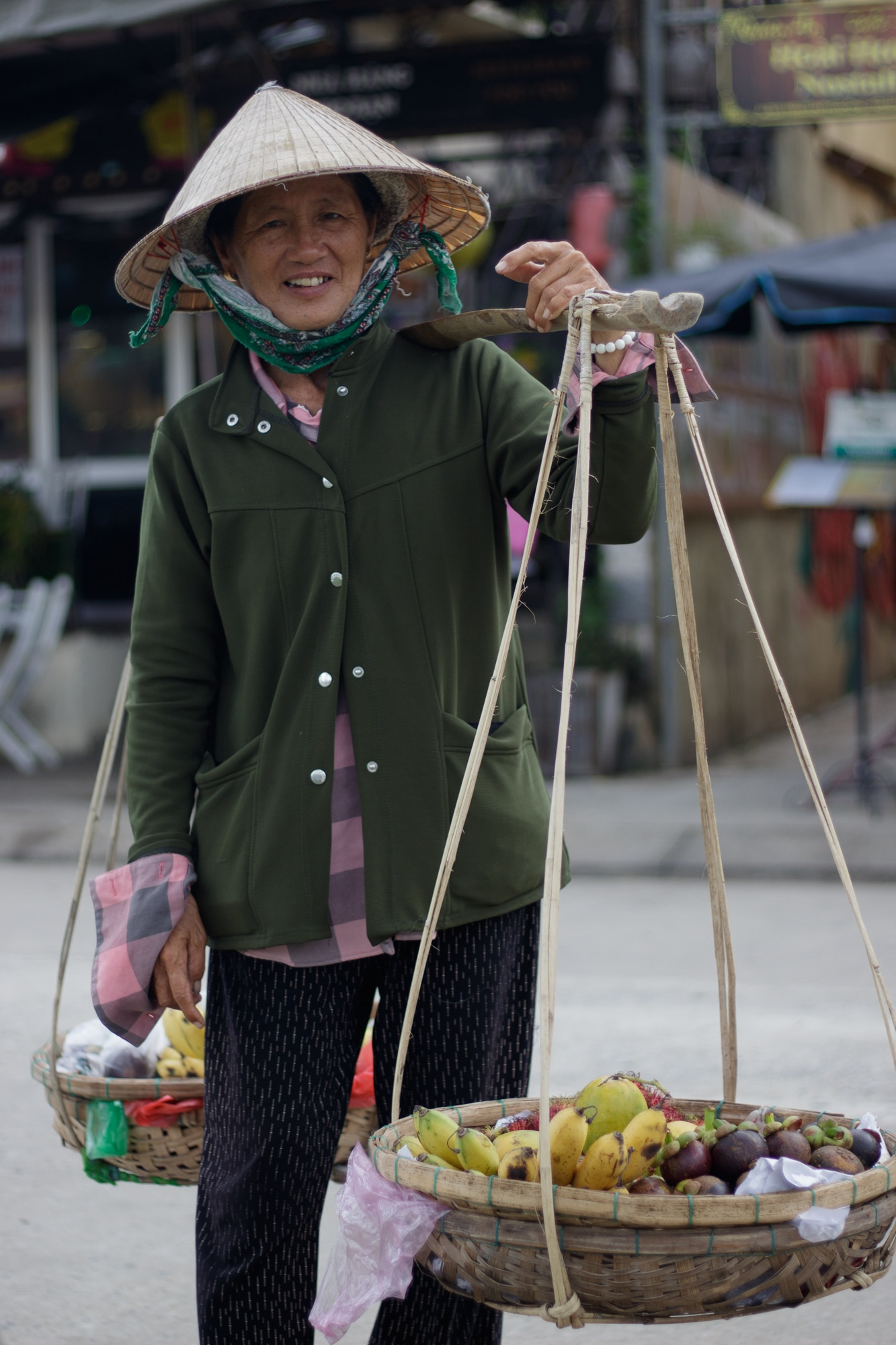 A fruit vendor poses for a picture in Hoi An, Vietnam.