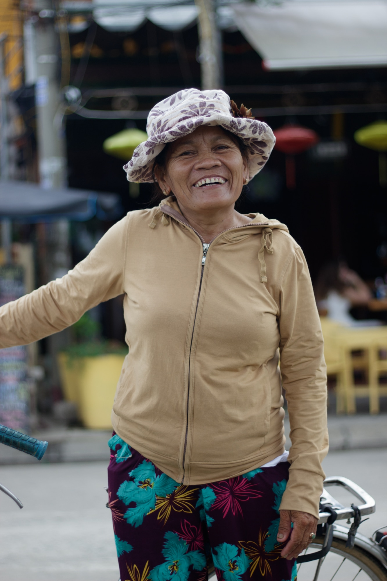 A woman in Hoi An, Vietnam smiles after she notices the camera.