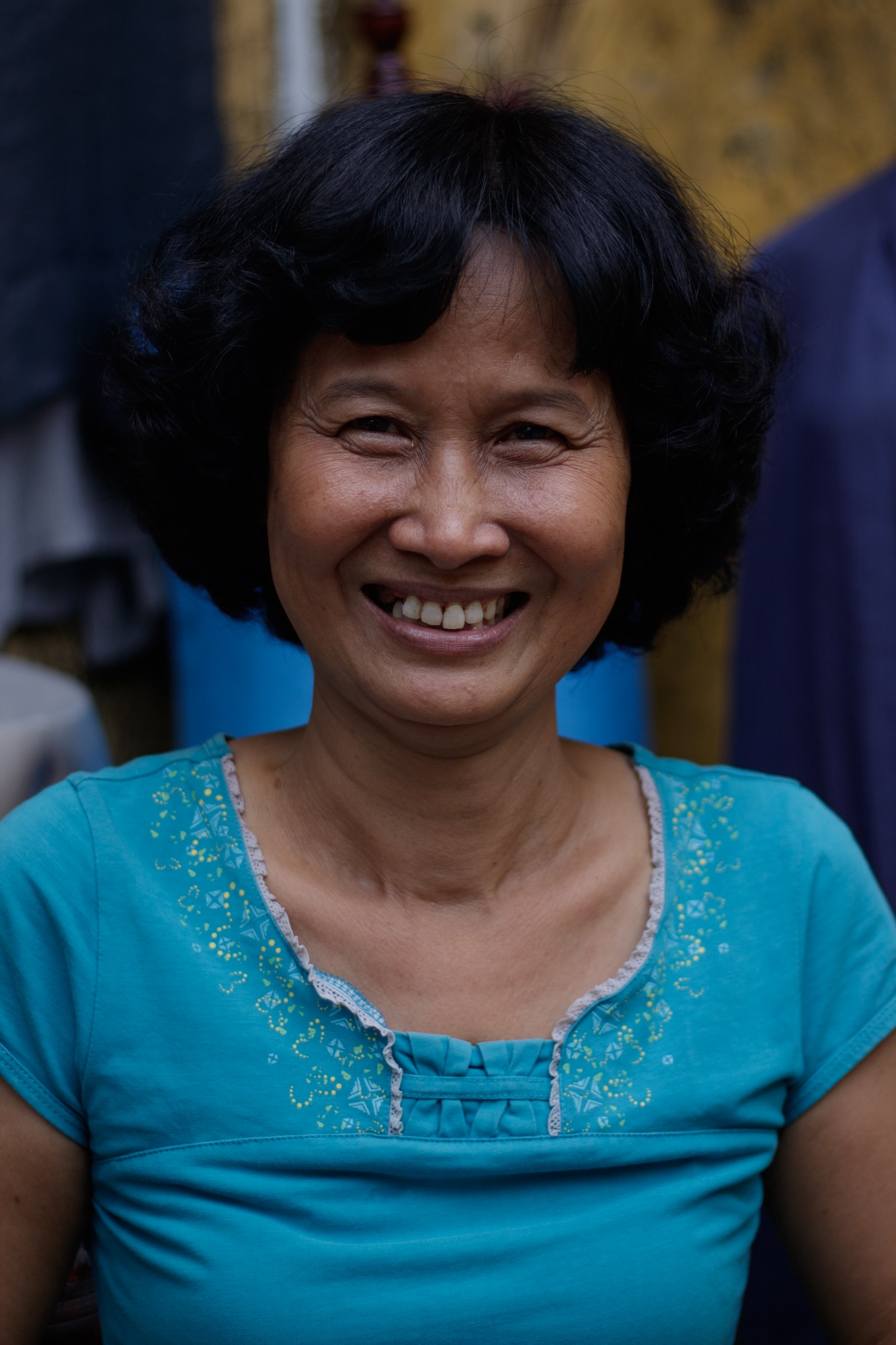 A diary vendor smiles at camera after a successful sale. Hoi An, Vietnam.