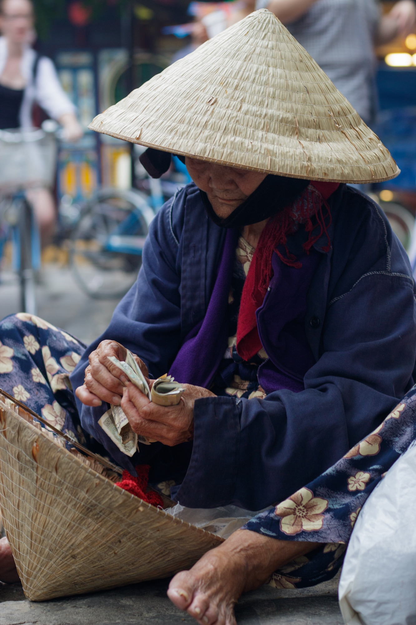 An elderly vendor counts money sitting on the side of the road in Hoi An.