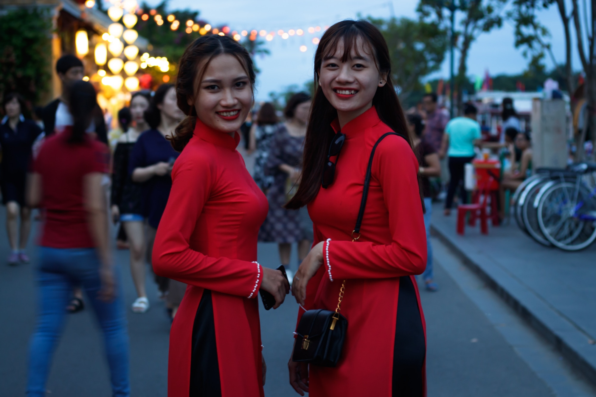Girls wearing Ao Dai costume pose for a picture in Hoi An.