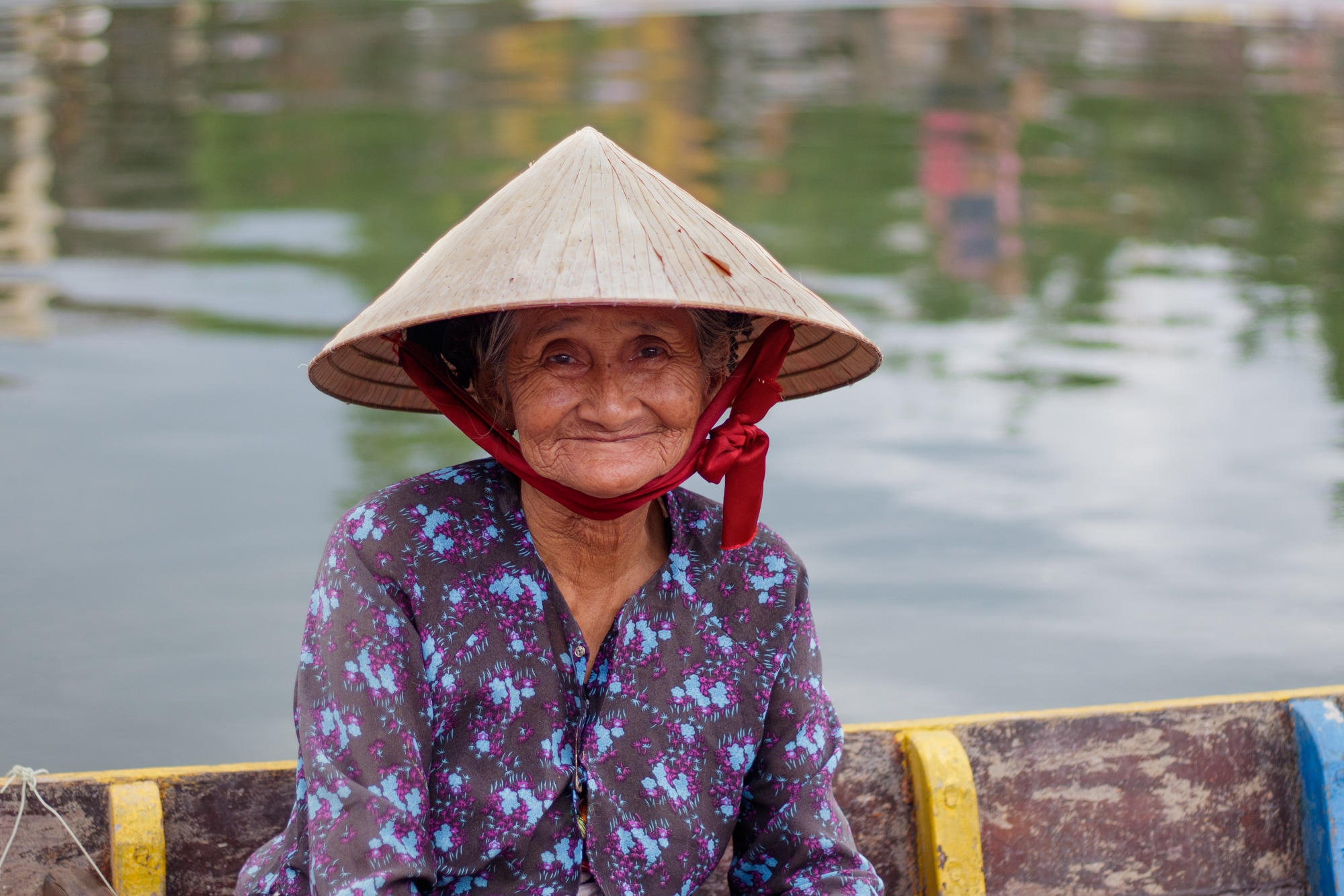 An elderly boat woman - probably the most recognisable face in Hoi An - smiles at camera.