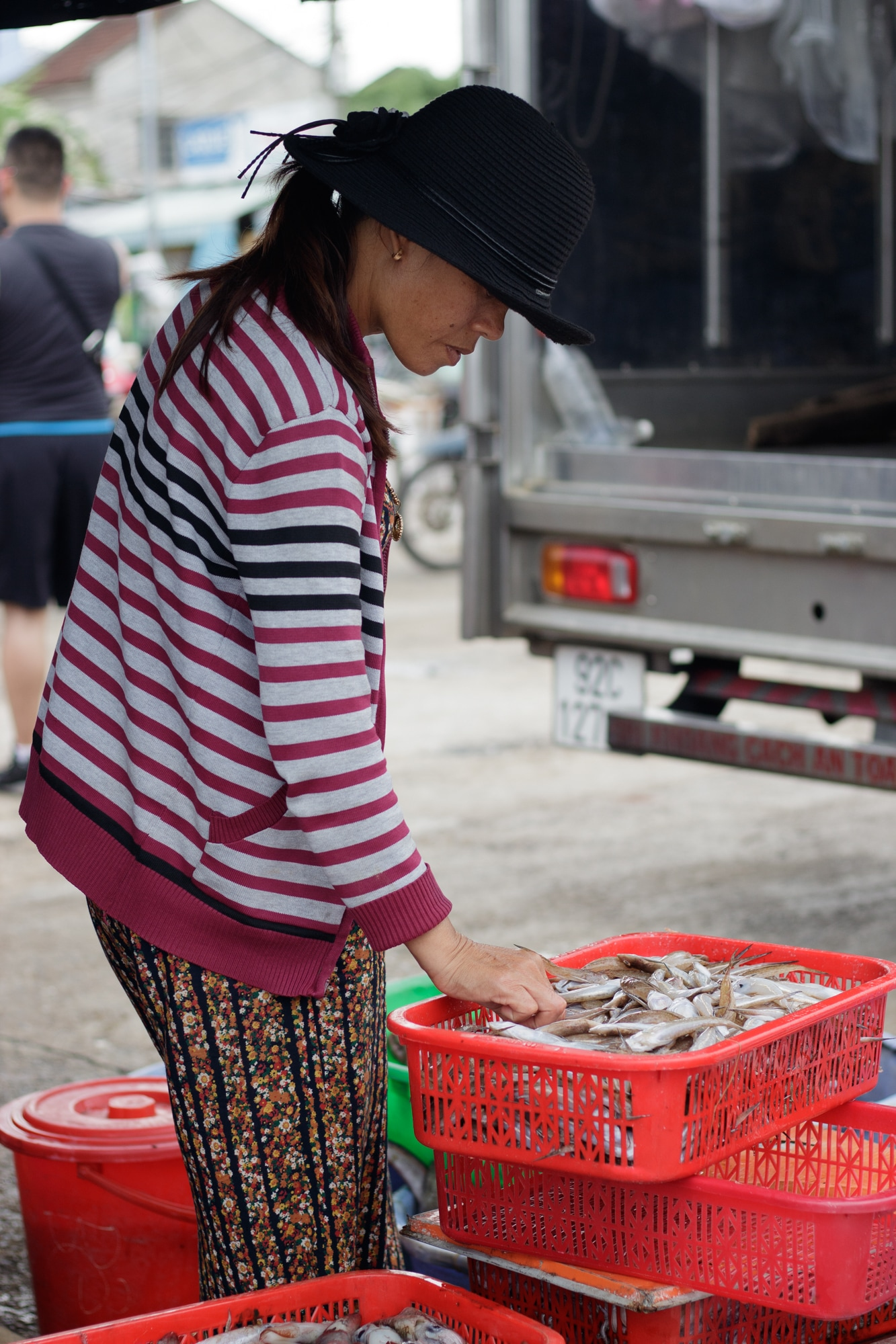 A fish seller inspects fish stock in Hoi An, Vietnam.
