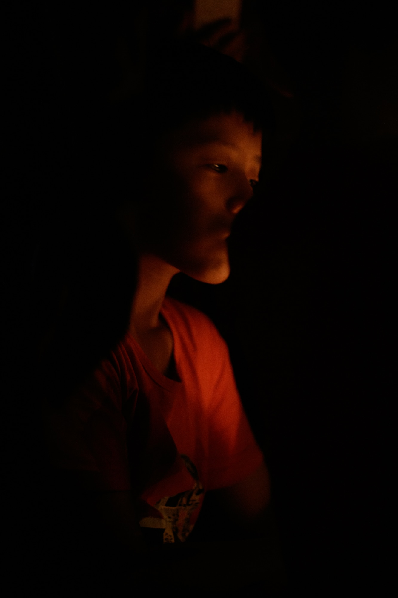 A boy lit by candle light photographed in Hoi An.